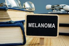 黑瘤疾病概念 书和玻璃在书桌上 免版税库存图片