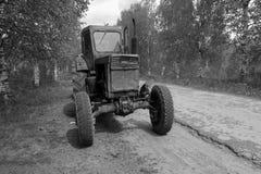 黑白农用拖拉机停放在路一边 免版税库存照片