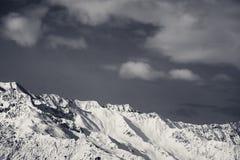 黑白冬天多雪的山和天空与云彩 免版税库存图片