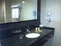 黑白口气的宽敞旅馆卫生间与清洁毛巾和hairdryer为对客人的使用 免版税图库摄影