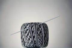 黑白毛线和钩针的汉克,在灰色 图库摄影