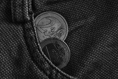 黑白照片与一和2在破旧的葡萄酒褐色牛仔布牛仔裤的口袋的欧元的衡量单位的两枚欧洲硬币 免版税库存图片