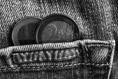 黑白照片与1和2在破旧的蓝色牛仔布牛仔裤的口袋的欧元的衡量单位的两枚欧洲硬币 库存图片