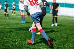 黑白色运动服奔跑的,一滴,对橄榄球场的攻击男孩 有球的年轻足球运动员在绿草 ?? 免版税图库摄影