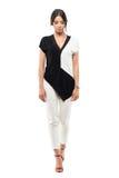 黑白衣服的看典雅的年轻的女商人走和下来 库存图片