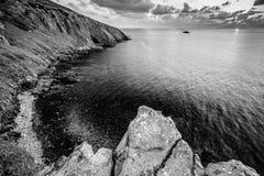 黑白风景、岩石海岸和多云天空 免版税库存照片