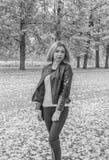黑白,在公园秋天天步行一个可爱的女孩 图库摄影