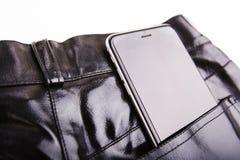 黑皮革布料片断的特写镜头与电话的 图库摄影