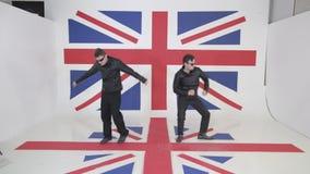 黑皮革摩托车夹克和太阳镜的两个精力充沛的逗人喜爱的人跳舞 股票视频