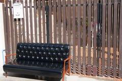 黑皮革沙发和木扶手椅子与白色邮箱在棕色背景 免版税库存图片