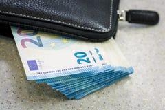 黑皮革钱包和一团现金20欧元是在灰色桌上的谎言 库存图片