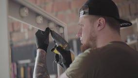黑盖帽的与纹身花刺的木匠和手套在把胶浆放的胳膊在镜子的木制框架上 工作者 股票视频