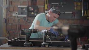 黑盖帽的把胶浆放的木匠和手套在木制框架上 使用硅树脂胶水枪的人在家具 股票录像