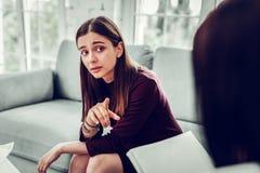 黑眼睛的妇女问有些问题对她的心理学家 库存照片