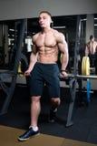 黑短裤的肌肉切细的坚强的赤裸上身的人与手表在健身房的酒吧停留 免版税库存图片