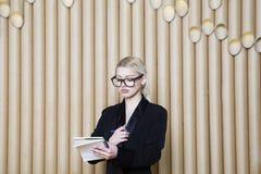 黑礼服和玻璃的美丽的惊奇白肤金发的女商人 免版税图库摄影