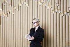 黑礼服和玻璃的美丽的惊奇白肤金发的女商人 免版税库存照片