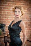 黑礼服摆在的年轻美丽的短发白肤金发的妇女 有电影明星神色的典雅的浪漫神奇夫人 免版税库存图片