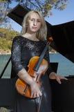 黑礼服的一个美丽的白肤金发的女孩有红色嘴唇的弹小提琴 免版税库存照片