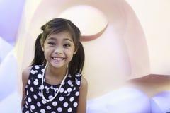 黑礼服的一个逗人喜爱的亚裔女孩有白色斑点和领带头发的享用与大玩偶 免版税库存图片