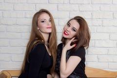 黑礼服的两个美丽的女孩坐长凳和闲话 免版税库存照片