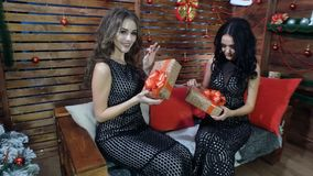 黑礼服的两个美丽的女孩有欢乐箱子的在他们的手上 库存照片
