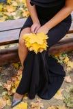 黑礼服的少女有橡木叶子的 图库摄影