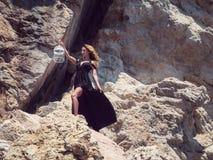 黑礼服的少妇在岩石 免版税库存图片