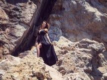 黑礼服的少妇在岩石 库存照片