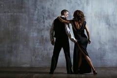 黑礼服的年轻俏丽的妇女和人跳舞探戈 库存图片