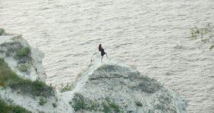 黑礼服跳舞的少妇在海的峭壁 股票录像