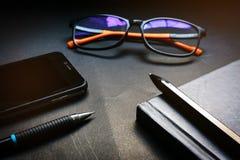 黑笔记本、玻璃、笔、铅笔和手机的关闭在剧烈的点燃的口气的黑书桌背景 公共汽车的概念 图库摄影