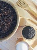 黑米,黑芝麻,糖,在一个木盘,安置在一个木盘子 图库摄影