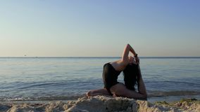黑紧身衣裤的健身妇女与一个运动的身体在海坐海滩并且做瑜伽和舒展 健身,体育,瑜伽 股票录像