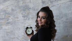 黑紧身衣裤的美丽的孕妇 她拿着在手符号暗示的时钟remanining的时间befour 影视素材