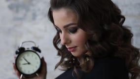 黑紧身衣裤的美丽的孕妇 她拿着在手符号暗示的时钟remanining的时间befour 股票视频