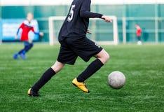 黑红色运动服奔跑的,一滴,对橄榄球场的攻击男孩 有球的年轻足球运动员在绿草 ?? 库存图片