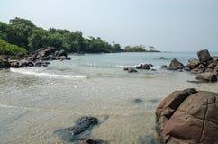 黑约翰逊海滩在塞拉利昂,有风平浪静、ropcks和离开的海滩的非洲 库存照片