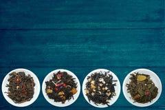 黑绿茶和品种在赠送者蓝色土气木背景的 库存照片