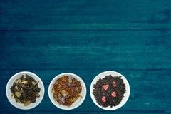 黑绿茶和品种在赠送者蓝色土气木背景的 库存图片