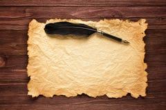 黑羽毛和老纸在一张棕色桌的背景 免版税库存照片
