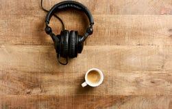 黑耳机和一杯咖啡在土气木背景的 免版税库存照片