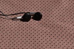 黑耳机在聚酯尼龙纤维棕色运动服说谎  听的概念到在训练wi的体育期间的音乐 库存图片