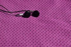 黑耳机在聚酯尼龙纤维紫色运动服说谎  听的概念到在训练w的体育期间的音乐 库存照片