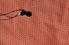 黑耳机在聚酯尼龙纤维红色运动服说谎  听的概念到在训练与的体育期间的音乐 库存照片