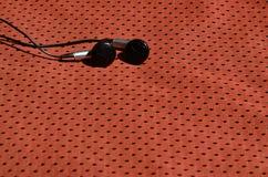 黑耳机在聚酯尼龙纤维红色运动服说谎  听的概念到在训练与的体育期间的音乐 图库摄影