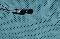黑耳机在聚酯尼龙纤维蓝色运动服说谎  听的概念到在训练机智的体育期间的音乐 免版税库存照片