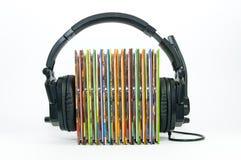 黑耳机,堆五颜六色的音乐cd 库存照片