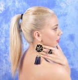 黑耳环的年轻美丽的女孩在抽象背景 免版税库存图片