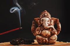 黑背景的印度神加内什 Rudraksha雕象和念珠在一张木桌上用一股红色香火棍子和香火烟 免版税库存照片
